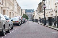 LONDRES, REINO UNIDO - 9 DE ABRIL DE 2013: Calle con solamente una persona Solamente coches y señales de tráfico que parquean Imágenes de archivo libres de regalías
