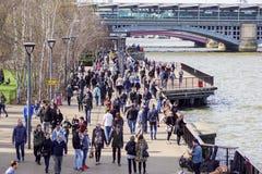 LONDRES, REINO UNIDO - 6 DE ABRIL DE 2017: Los turistas caminan abajo de la trayectoria alineada árbol en el southbank del río Tá Foto de archivo libre de regalías
