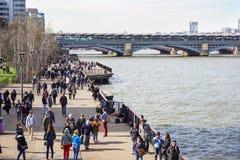 LONDRES, REINO UNIDO - 6 DE ABRIL DE 2017: Los turistas caminan abajo de la trayectoria alineada árbol en el southbank del río Tá Fotos de archivo libres de regalías