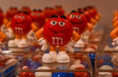 Londres, Reino Unido - 7 de agosto de 2018: Doces de chocolate coloridos do ` s de M&M em uns recipientes plásticos, com a mascot foto de stock