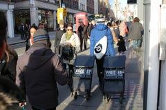 LONDRES, Reino Unido - 16 de febrero de 2018: Estantes de periódicos de fricción del muchacho de periódico en la calle foto de archivo libre de regalías