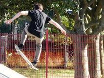 Londres, Reino Unido - 28 de junio de 2018: una juventud masculina desconocida realiza trucos del monopatín en un parque local de Foto de archivo libre de regalías