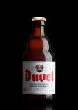 LONDRES, REINO UNIDO - 30 DE MARZO DE 2017: Botella de cerveza de Duvel en negro Duvel es una cerveza inglesa de oro fuerte produ Fotografía de archivo libre de regalías