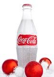 LONDRES, REINO UNIDO - 7 DE NOVIEMBRE DE 2016: Botella clásica de Coca-Cola en el fondo blanco con los juguetes y la nieve de la  Imagen de archivo
