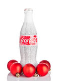 LONDRES, REINO UNIDO - 11 DE NOVIEMBRE DE 2016: Botella clásica de Coca-Cola en el fondo blanco con los juguetes y la nieve de la Foto de archivo libre de regalías