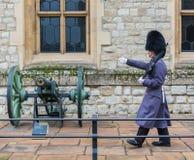 LONDRES, REINO UNIDO - 24 DE NOVIEMBRE DE 2018: Guardia real en la torre de Londres Marchas jovenes del soldado cerca de un arma fotos de archivo libres de regalías