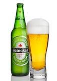 LONDRES, REINO UNIDO - 23 DE OCTUBRE DE 2016: Botella de Heineken Lager Beer con el vidrio en el fondo blanco Heineken es el prod Fotografía de archivo libre de regalías