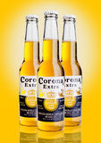 LONDRES, REINO UNIDO - 23 de octubre de 2016: Botellas de Corona Extra Beer en fondo amarillo Corona, producida por el ingenio de Foto de archivo libre de regalías