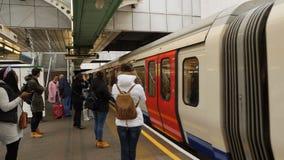 Londres, Reino Unido - 20 de octubre de 2017: Gente que espera en la plataforma subterráneo del tubo tren al undergroun de Hammer almacen de video