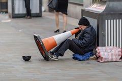 Londres, Reino Unido - 17, diciembre de 2018: Vista lateral de un mendigo masculino que se sienta en la calle cerca de la taza di imágenes de archivo libres de regalías