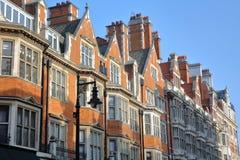 LONDRES, REINO UNIDO: Fachadas victorianas de las casas del ladrillo rojo en la ciudad de la calle del soporte de Westminster imagen de archivo libre de regalías