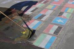 Londres, REINO UNIDO, 09 04 2016 Uma limpeza do homem indica as bandeiras feitas do giz, simbolizando a crise dos estados-nação Imagem de Stock