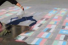 Londres, REINO UNIDO, 09 04 2016 Una limpieza del hombre indica las banderas hechas de tiza, simbolizando crisis de las naciones  Foto de archivo libre de regalías