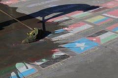 Londres, REINO UNIDO, 09 04 2016 Una limpieza del hombre indica las banderas hechas de tiza, simbolizando crisis de las naciones  Fotos de archivo libres de regalías