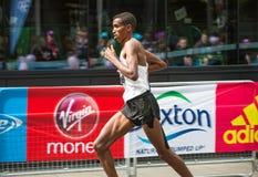 Londyński maraton Fachowy szybkobiegacz przyjeżdża pierwszy w Canary Wharf london wielkiej brytanii Obrazy Stock