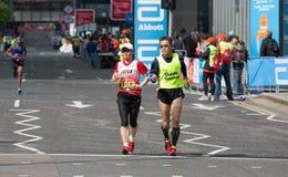 Londyński maraton, niepełnosprawna atleta bieg odległość z przewdoników biegaczami w Canary Wharf Zdjęcia Royalty Free
