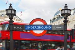 Londyński metro znak z latarniami ulicznymi i czerwonym autobusowym tłem obraz stock