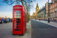 Londyn, Anglia - Tradycyjny Stary Brytyjski czerwony telefoniczny pudełko przy Wiktoria bulwarem z Big Ben obrazy stock