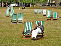 Londyn A mężczyzna znalezisko relaksuje odpoczywać na pokładu krześle w Hyde parku Zdjęcia Stock