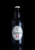 LONDYN, UK - LISTOPAD 29, 2016: Guinness ekstra korpulentna piwna butelka na czarnym tle Guinness piwo produkuje od 1759 Obrazy Stock