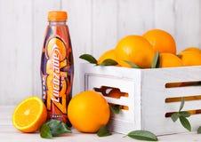 LONDYN, UK - MARZEC 31, 2018: Plastikowa butelka Lucozade pomarańcze zero miękki napój z świeżymi surowymi pomarańczami w drewna  fotografia stock