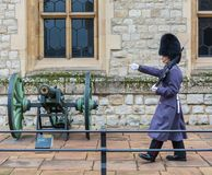LONDYN ZJEDNOCZONE KRÓLESTWO, LISTOPAD, - 24, 2018: Królewski strażnik przy wierza Londyn Młody żołnierz maszeruje blisko pistole zdjęcia royalty free