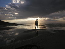 Lone. Female figure on sunset beach royalty free stock photography