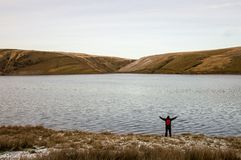 A lone backpacker with arms outstretched standing on the edge of a reservoir looking out on bleak moorland in winter. Elan Valley,. Wales. UK royalty free stock image