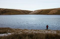 A lone backpacker standing on the edge of a reservoir looking out on bleak moorland in winter. Elan Valley, Wales. UK.  royalty free stock photos
