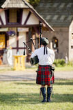Lone Bagpiper Playing. A lone bagpiper in kilt playing outside Royalty Free Stock Photography
