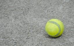 Lone baseball. Yellow baseball on gravel field Royalty Free Stock Image