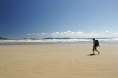 Lone Beach walk. Two hikers walking up a sandy beach with deep blue sky behind them Royalty Free Stock Image