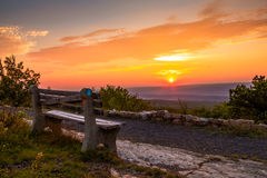 A lone bench looks over the mountain at sunset next to rock wall Royalty Free Stock Images