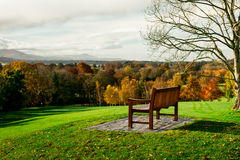 Lone bench overlooking distant mountains Stock Image