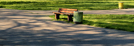 A lone bench in a park. Single bench placed beside an empty park walk. A wooden bench amid mowed grass royalty free stock photography