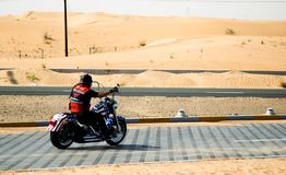 Desert Lone Biker. A lone biker on his Harley riding in desert road with sand dunes in the background royalty free stock photos