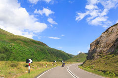 Lone Biker. A biker riding alone on mountainous road in Scotland Royalty Free Stock Photos