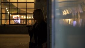 Lone blonde woman standing near disco hall and typing message on smartphone. Stock footage stock video