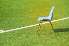 The lone blue chair is at the edge of the white line on the football field stock photo