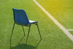 The lone blue chair on green at the football field stock image