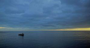 A lone boat is moored on a flat sea at sunrise stock photo