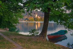 Lone boat moored near tree on Lake Bled, Slovenia at summer sunny morning royalty free stock photo