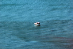 Lone boat in the sea. Lone boat in the blue sea Royalty Free Stock Photos