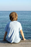 Lone boy. Little boy sitting alone on the end of a pier Royalty Free Stock Image