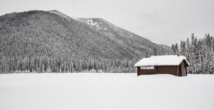 Lone Building Covered in Snow and Mountains Royalty Free Stock Image