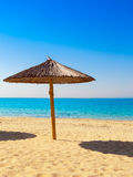 Lone Cane umbrella on the beach near the blue sea ... Royalty Free Stock Image