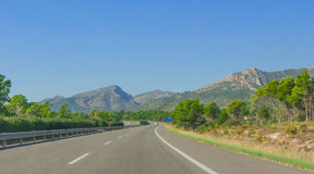 Lone car goes down the highway through coastal foothills and mountains of rural Spain. Sunshine on Coastal highway.  Lone white car drives along through Stock Photo