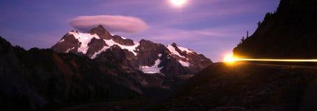 Lone Car Passes on Roadway Full Moon Mt Shuksan Royalty Free Stock Images