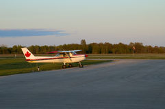 Lone Cessna. Profile view of a Cessna parked near an airport runway during sunset.  All logos and registrations removed - only generic canadian maple leaf left Royalty Free Stock Image