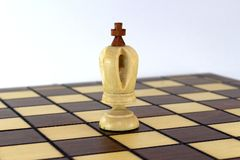 Lone chess white king on a chessboard over white background. Lone chess white king on a chessboard on white background close-up Royalty Free Stock Photos
